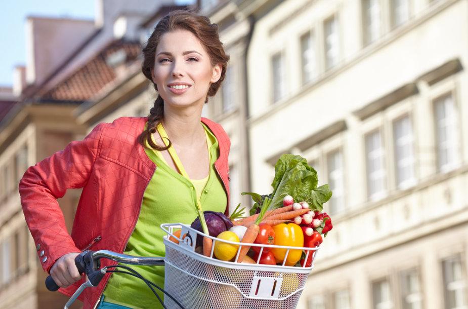 Moteris su daržovių krepšiu.