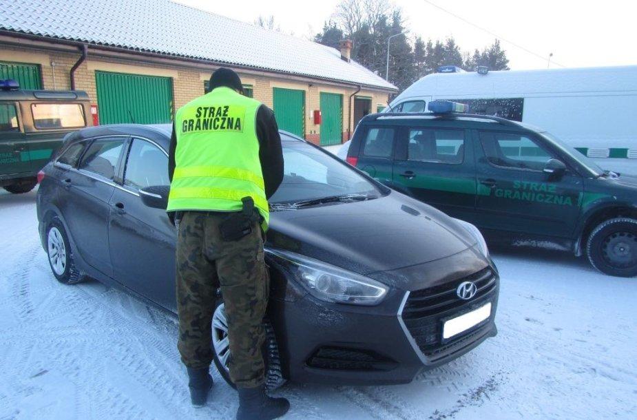 Lenkijos pareigūnas prie vogto automobilio.