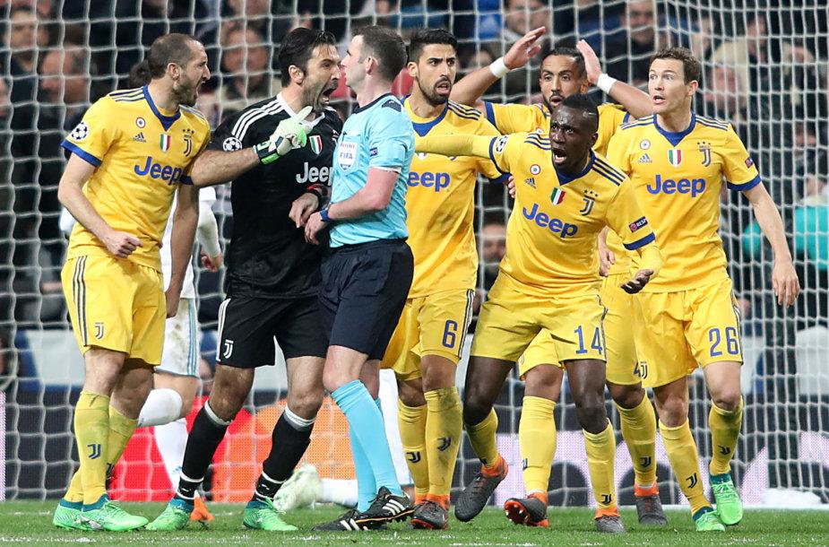 """""""Juventus"""" žaidėjai apsupo teisėją M.Oliverį per Čempionų lygos rungtynes su Madrido """"Real""""."""