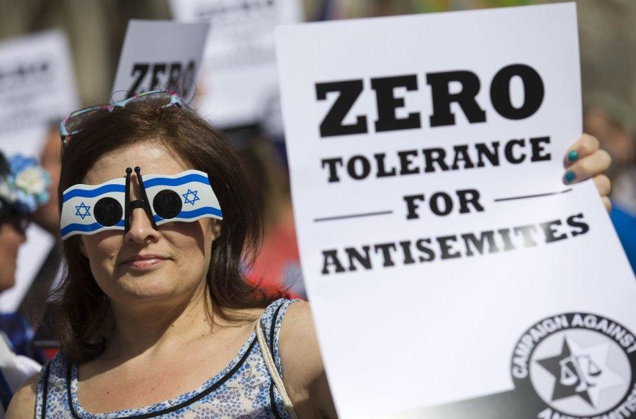 Prieš antisemitizmą protestuojanti moteris