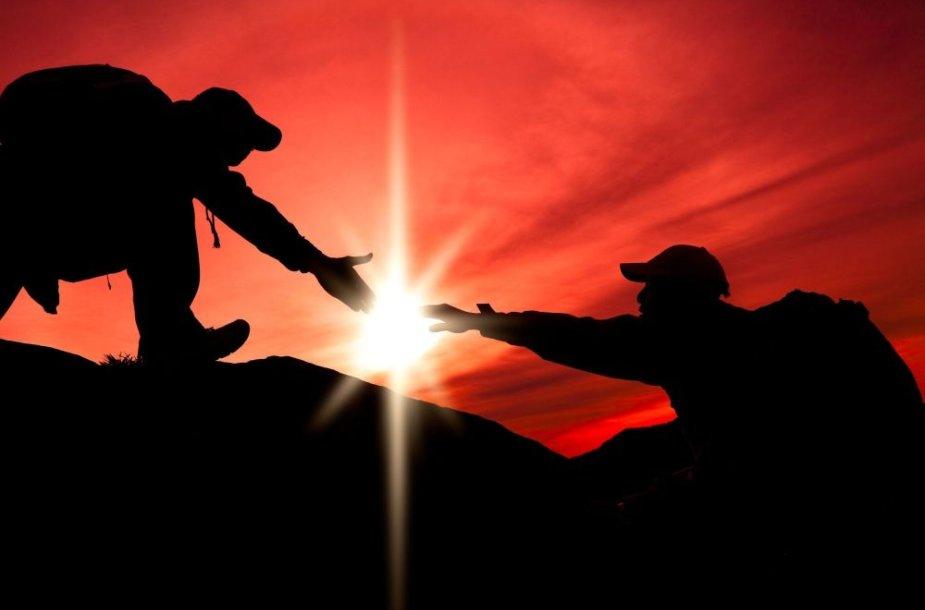 Žmogus tiesia pagalbos ranką kitam žmogui