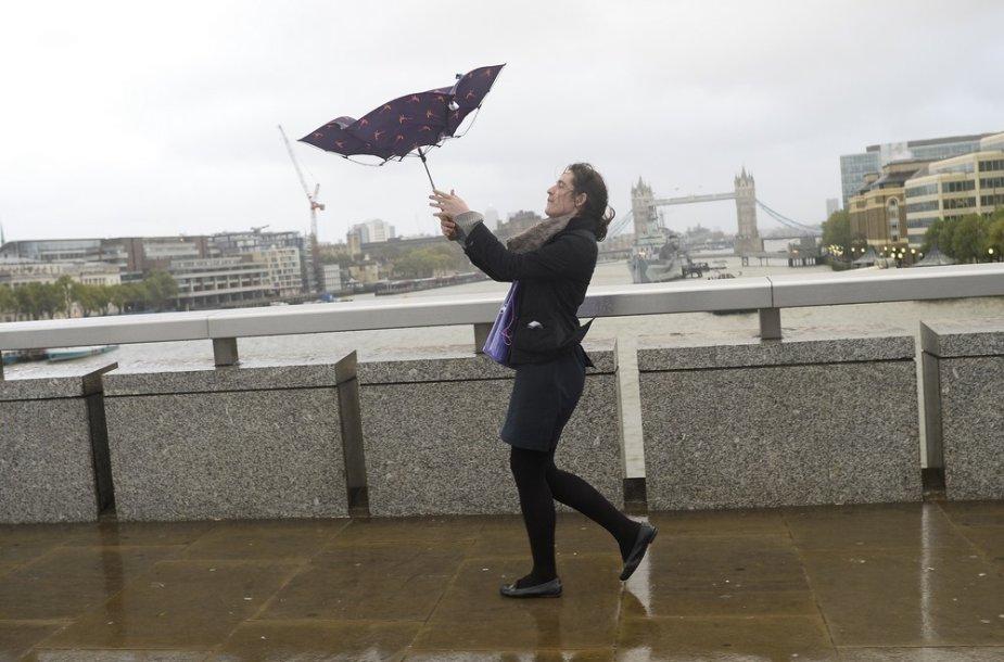 Stiprus vėjas plešia skėti iš moters rankų.