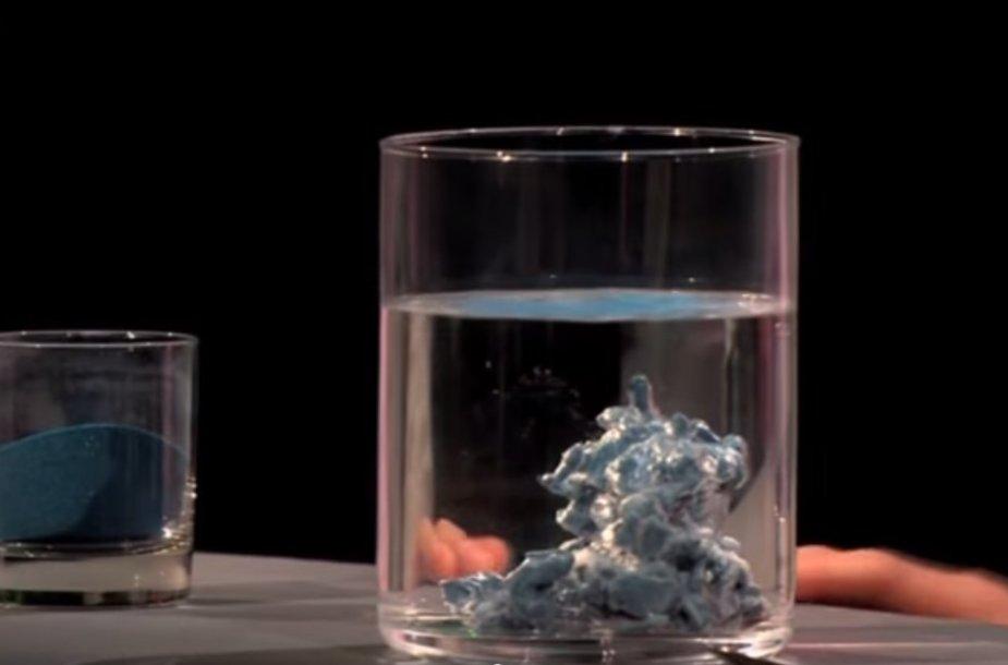 Vandens stiklinė, kurios apačioje guli hidrofobinis smėlis