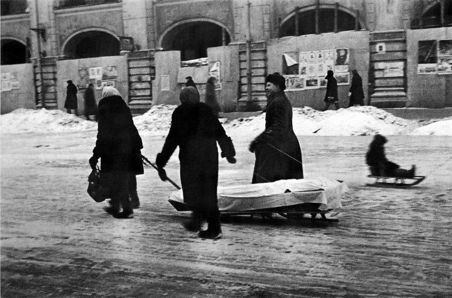 Giminaičiai veža į kapines mirusį šeimos narį.