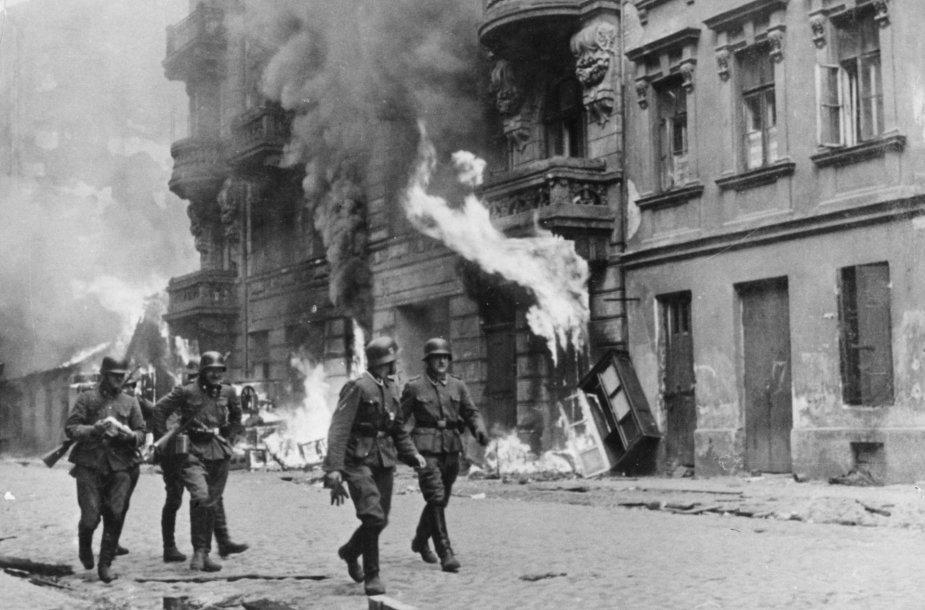 Vokiečių kareiviai 1943 m. eina pro padegtą Varšuvos getą, kuris po sukilimo buvo sudegintas iki pamatų