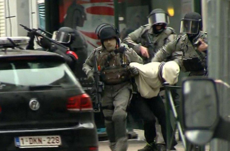 Belgijos policininkai veda penktadienį sulaikytą asmenį.