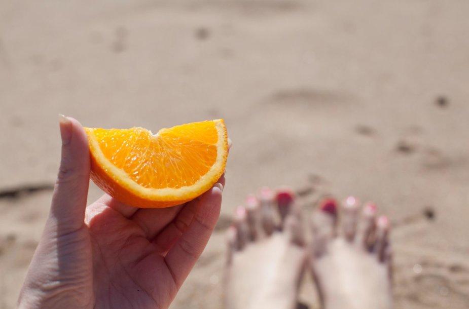 Moteris užkandžiauja apelsinu
