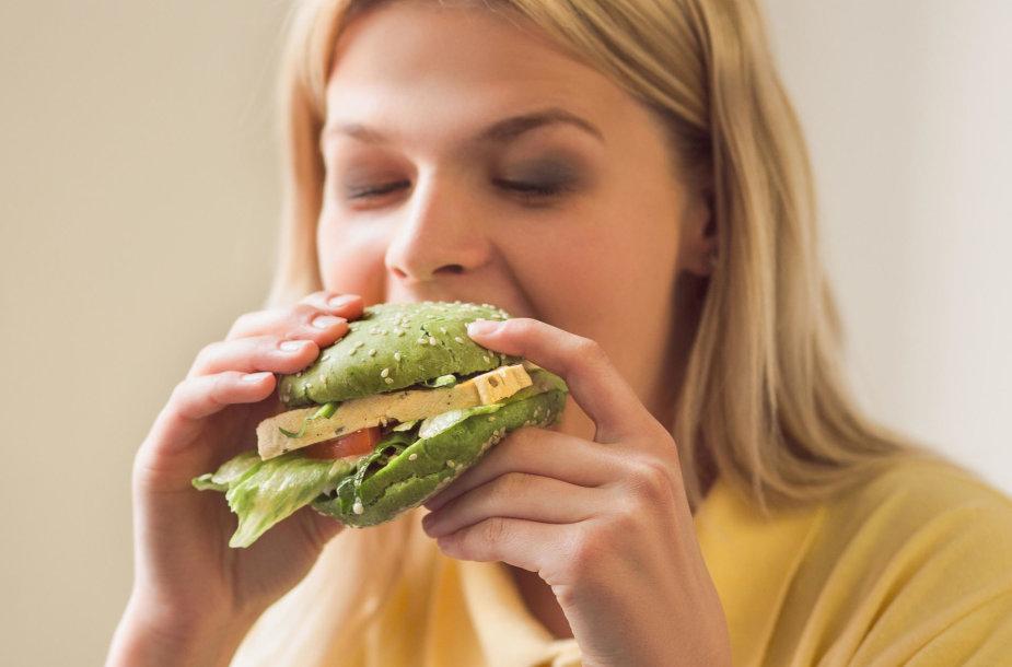 Moteris valgo veganišką burgerį