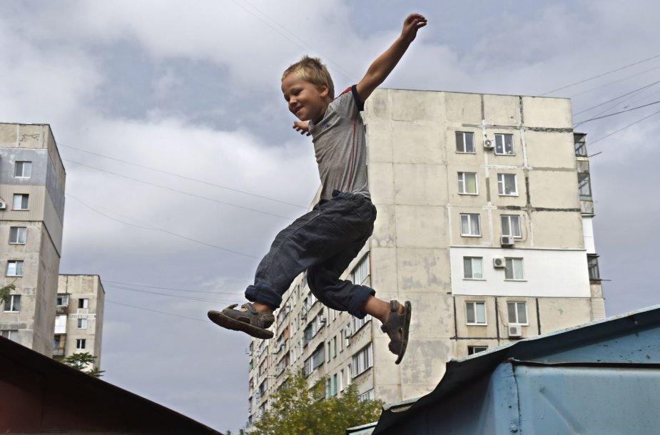 Mariupolyje berniukas šokinėja ant metalinių garažų stogų
