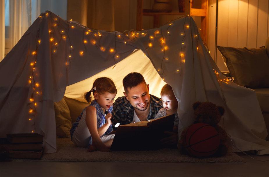 Tėtis skaito vaikams knygą