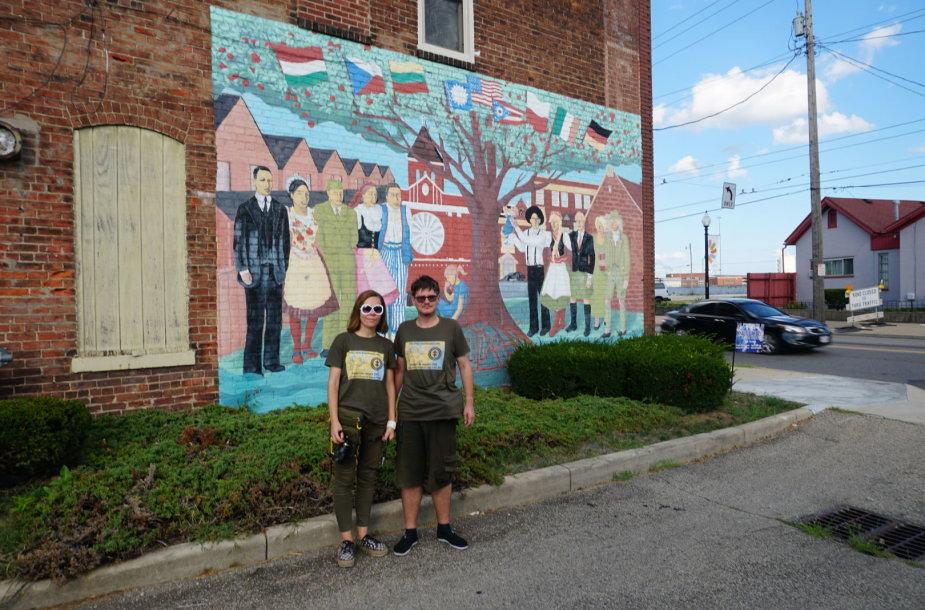 """""""Tikslas - Amerika"""" dalyviai prie įvažiavimo į Deitono miestą, kuriame pavaizduotos didžiausios miestą sudariusios tautinės grupės"""