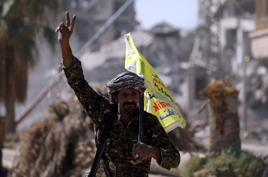 Sirijos pajėgų karys rodo pergalės ženklą buvusioje IS sostinėje Rakoje