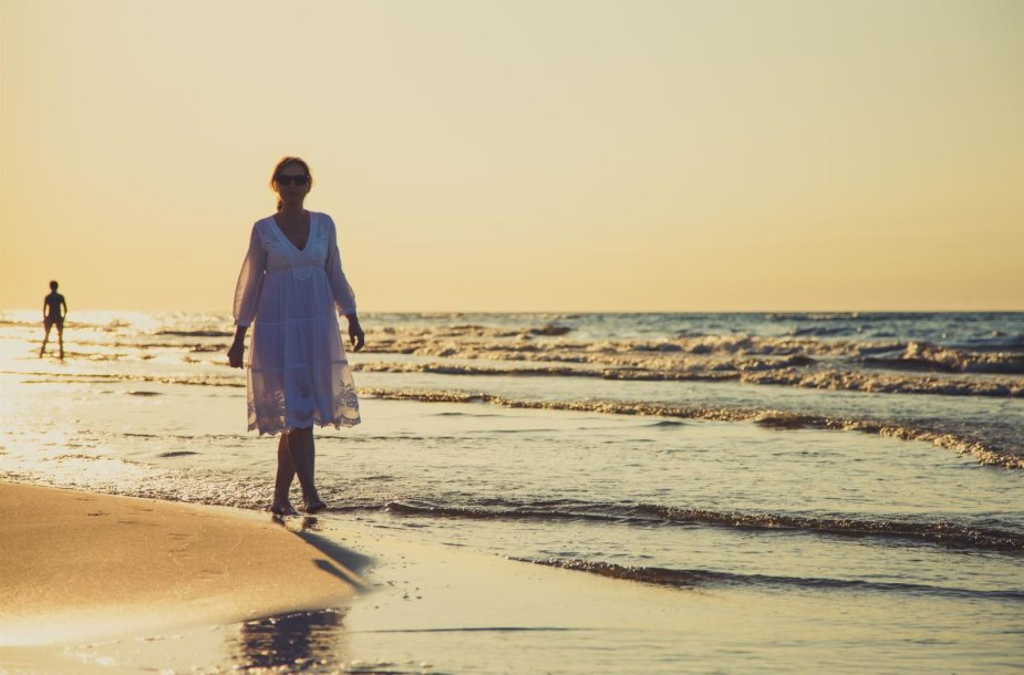 Moteris, einanti paplūdimiu