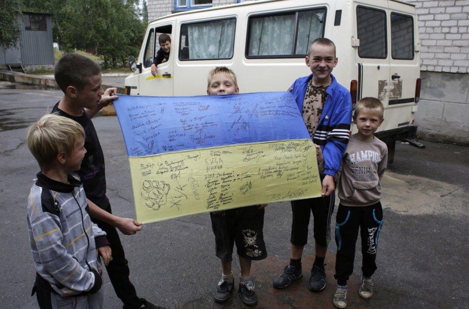 Vaikai rodo Ukrainos vėliavą su savanorių karių parašais