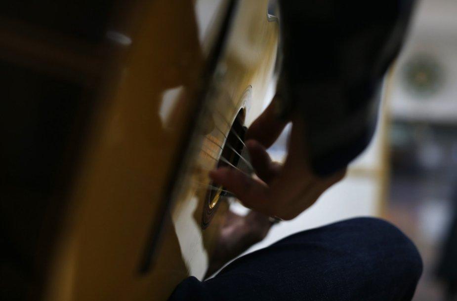 Klientas išmėgina gitarą