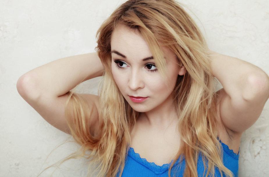 Mergina susirūpinusi plaukų būkle