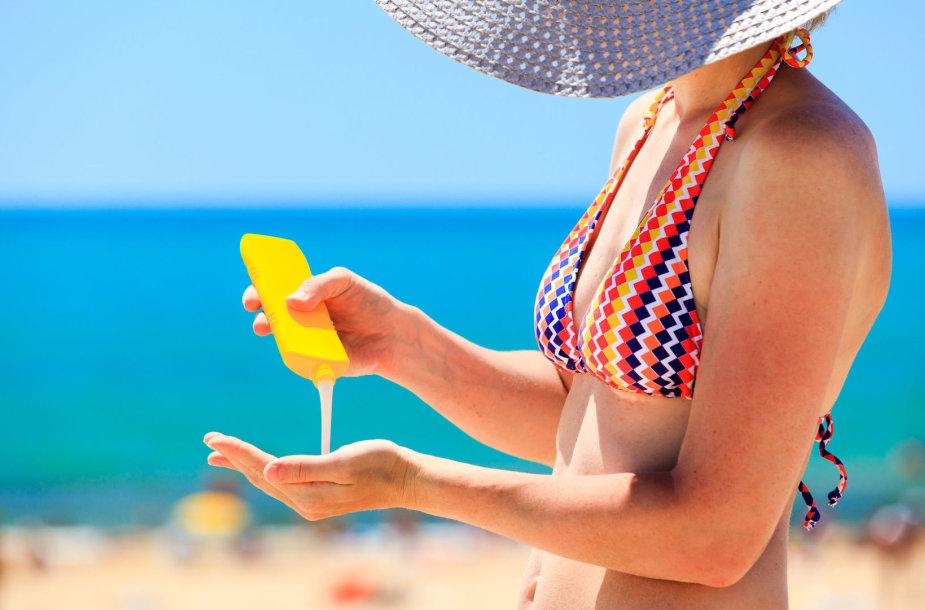 Moteris tepasi apsauginiu kremu nuo saulės