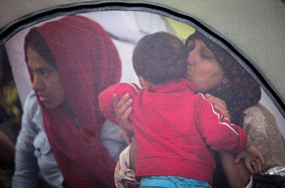 Migrantai šalia Lesbo salos uosto laukia kelto į Atėnus.