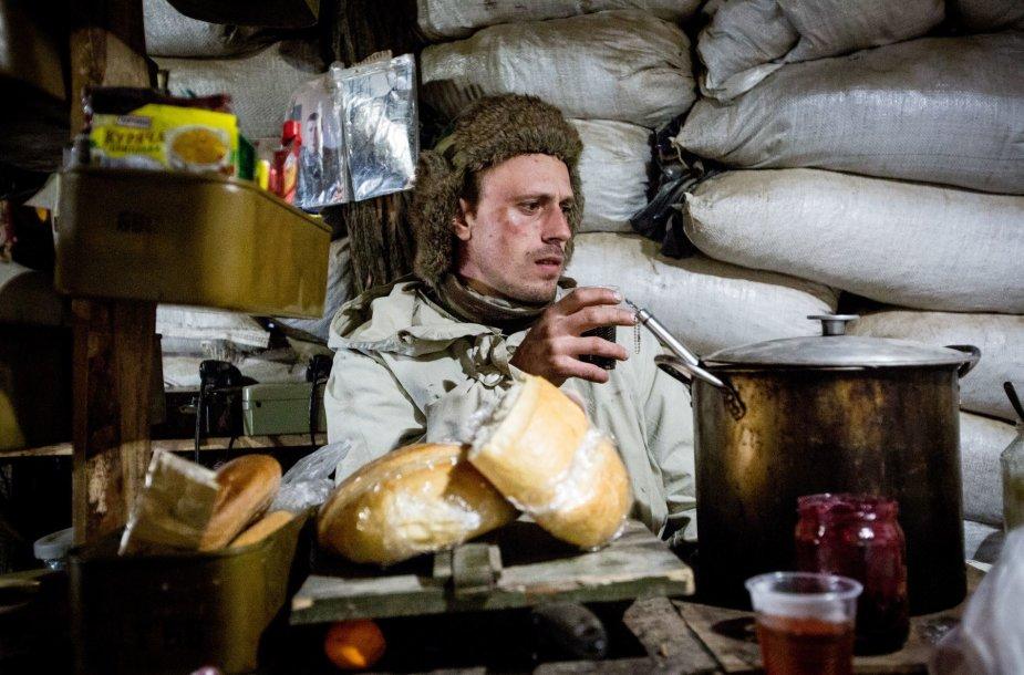 """Karys šaukiniu """"Tol"""" sėdi prie stalo apkasuose įrengtoje virtuvėje"""