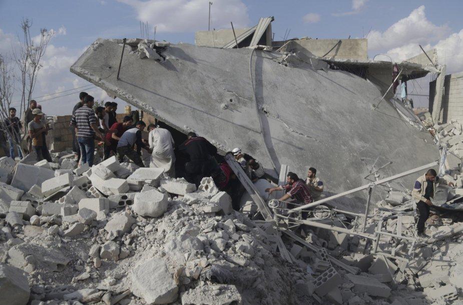 Vyrai ieško sužeistųjų tarp griuvėsių po Rusijos pajėgų bombardavimo