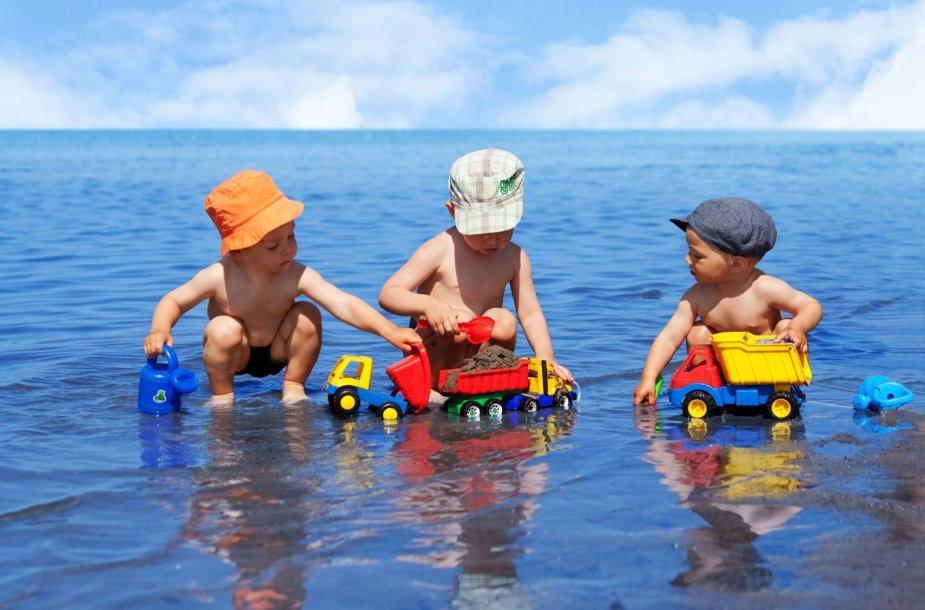 Trys berniukai žaidžia paplūdimyje
