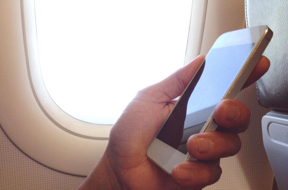 Telefonu besinaudojantis lėktuvo keleivis
