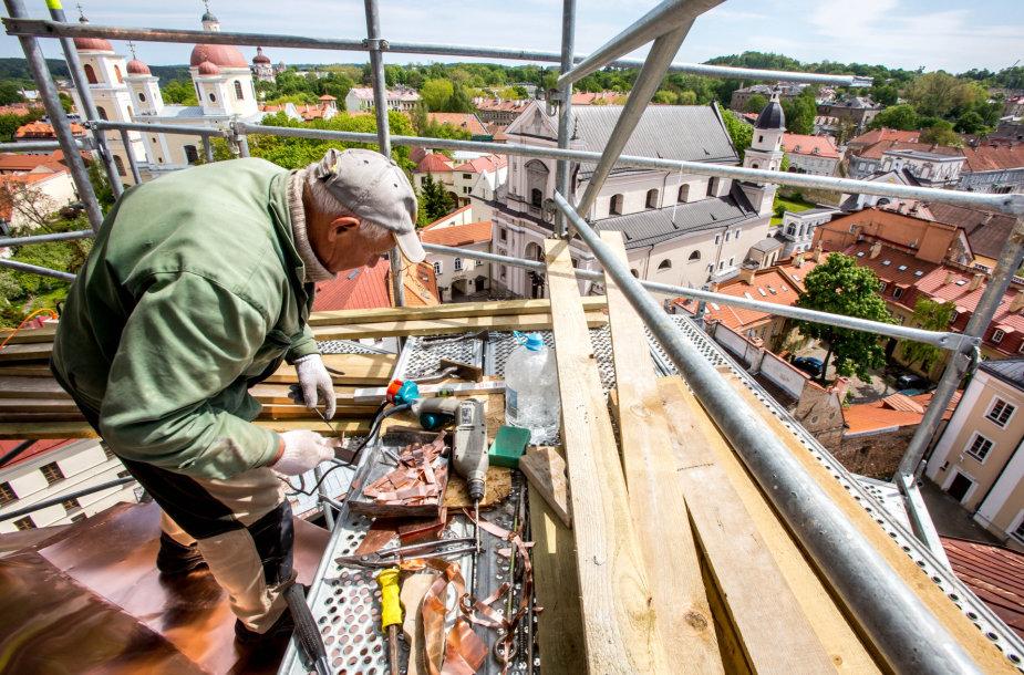 Aukštybėse dirbantys statybininkai tvarko unitų bažnyčios bokštą
