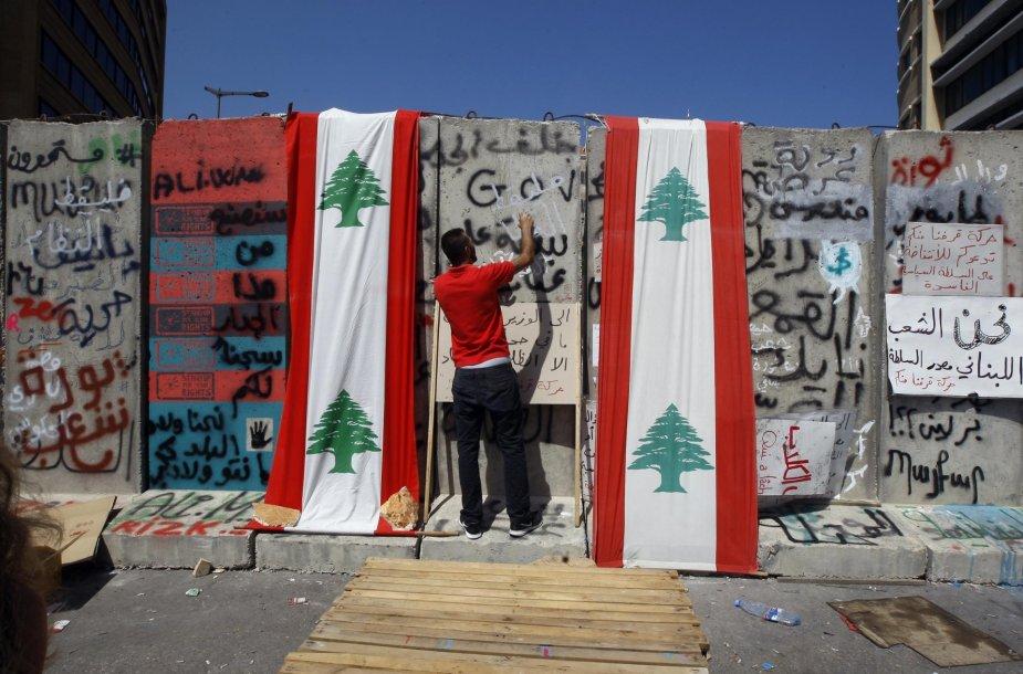 Protestuotojas prie sienos, skiriančios žmones ir vyriausybės rūmus
