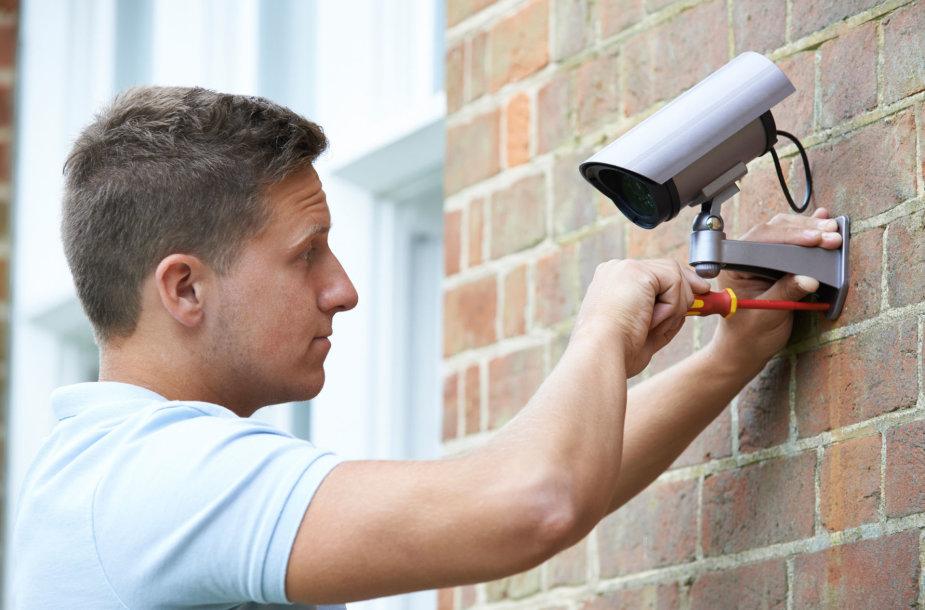 Vyras montuoja vaizdo stebėjimo kamerą.