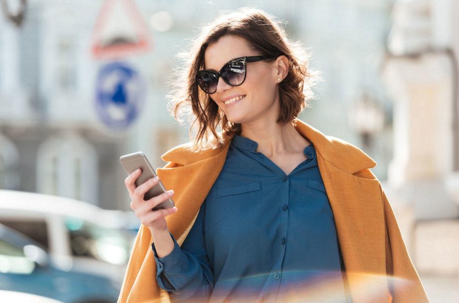 Moteris naudojasi mobiliuoju telefonu
