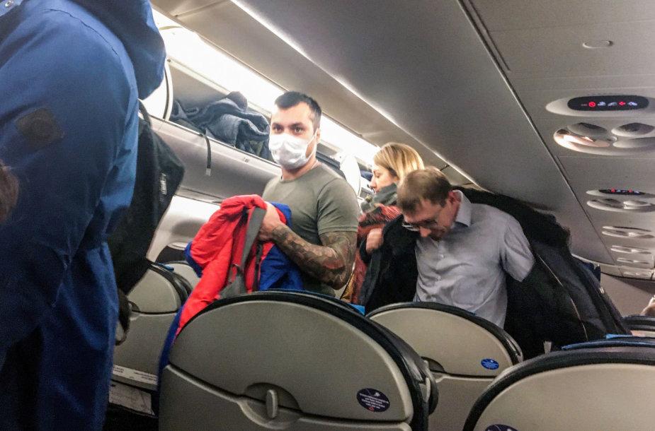 Žmonės lėktuve su apsauginėmis kaukėmis
