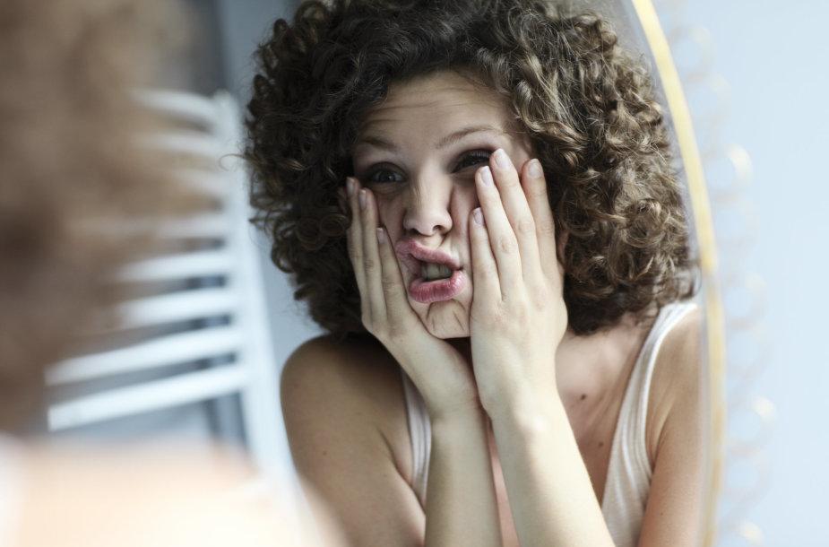 Moteris žiūri į veidrodį