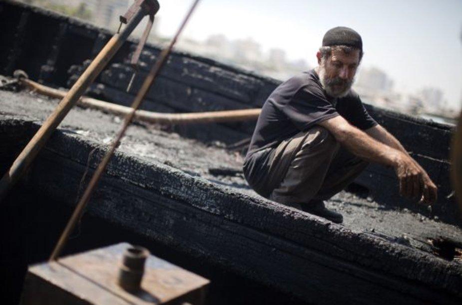 Palestinos žvejys prie sudegusios valties
