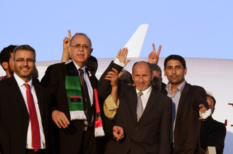 Mustafa Abdul-Jalilis (antras iš dešinės) lipa iš lėktuvo Tripolyje.