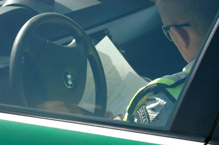 Policininkas rašo protokolą