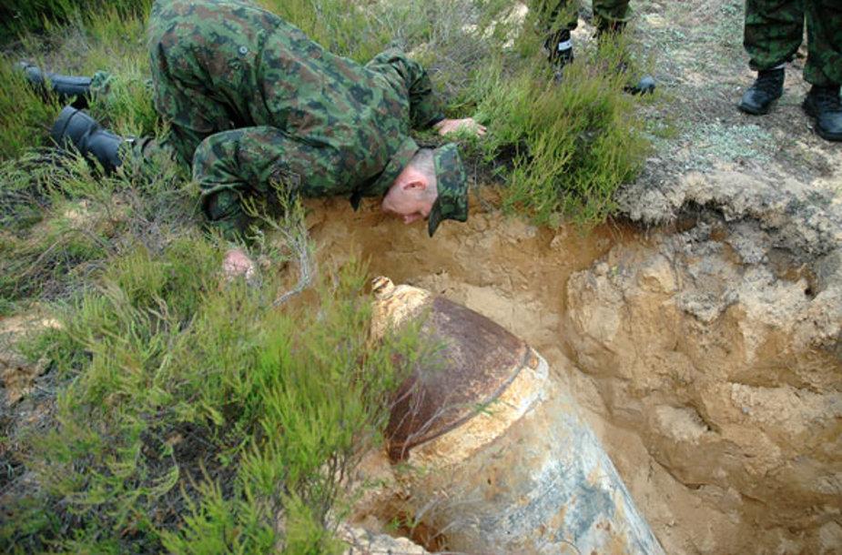 Išminuotojas buvusiame Rūdninkų poligone apžiūri rastą bombą. Sprogmenų Rūdninkuose randama nuolat.