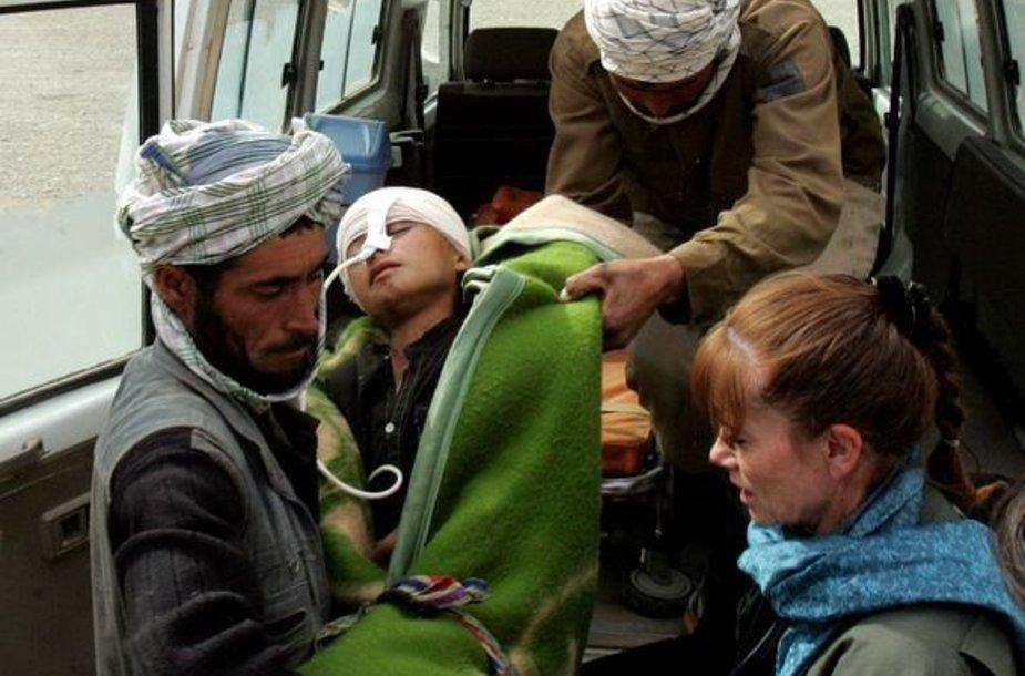 Sunkiai sužalotas afganistaniečių berniuką tėvas neša į sreigtasparnį.