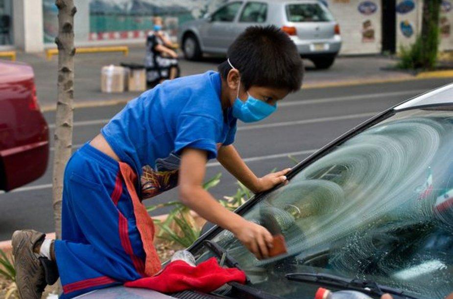 Berniukas užsidengęs veidą uždarbiauja gatvėje.