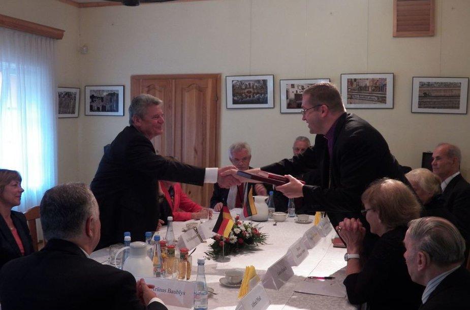 Rankas spaudžia Vokietijos prezidentas Joachimas Gauckas ir vyskupas Mindaugas Sabutis.