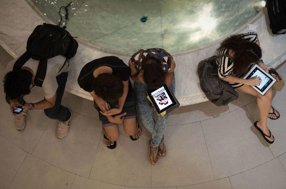 Žmonės naudojasi išmaniaisiais telefonais ir planšetiniais kompiuteriais