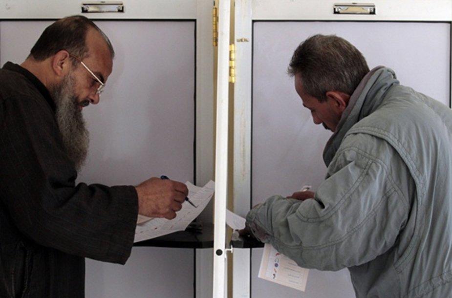 Vyrai pildo balsavimo biuletenius.
