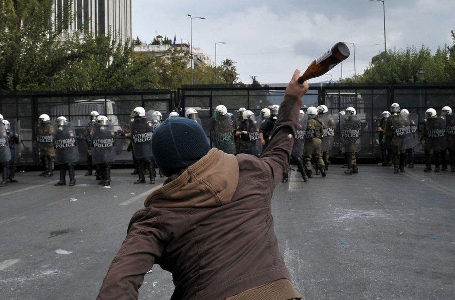 Protestuotojas meta butelį į policininkus.