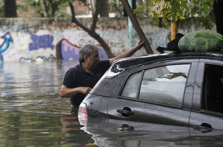 Vyras prie apsemto automobilio