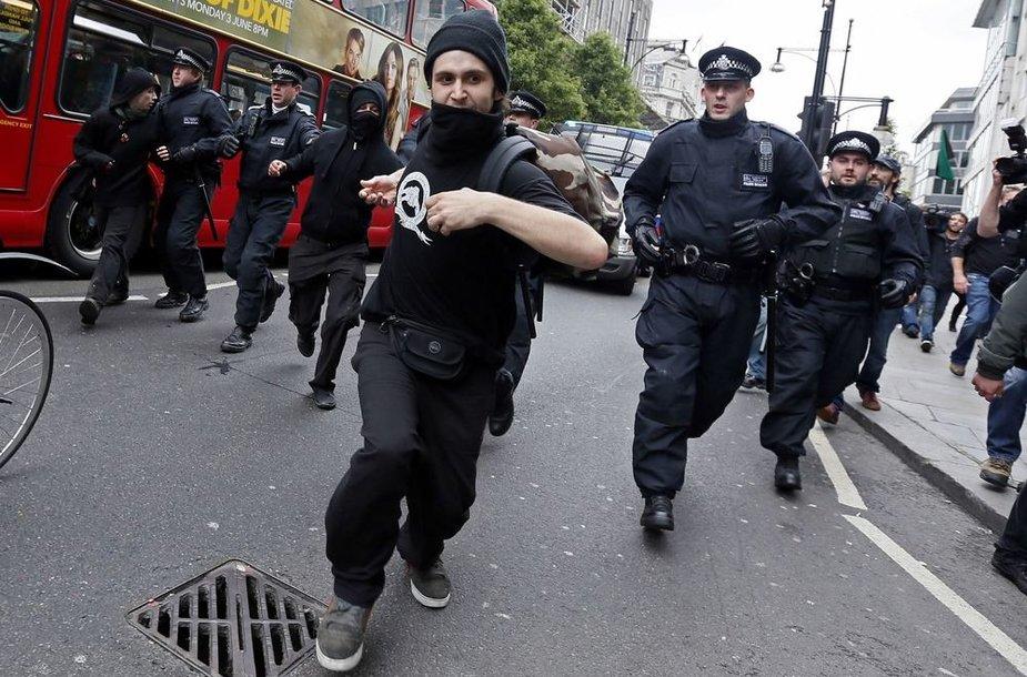 Nuo policijos bėgantis protestuotojas