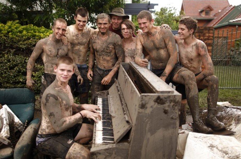 Vaikinai pozuoja prie purvino pianino
