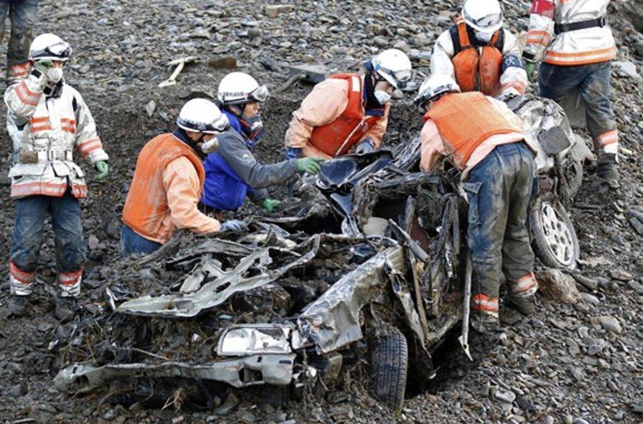 Gelbėtojai prie sulamdyto automobilio.
