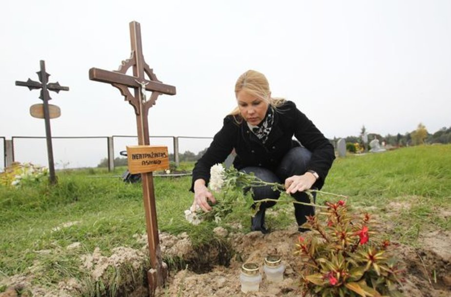 O.Artiomova nežino, ar gėles deda ant motinos, ar ant svetimo kapo.