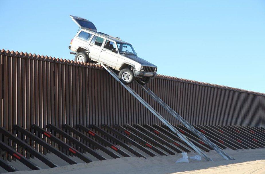 Kontrabandininkų džipas liko pakibęs ant 4,2 metrų aukščio tvoros, skiriančios Meksiką ir Ameriką.