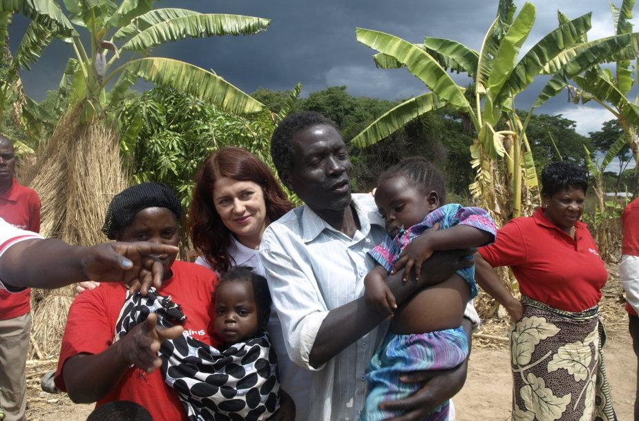 """Kartu su 11 vaikų šeima Kangalati kaimelyje: tėvas Selezani Mbewe su žmona ir dviem vaikais. Ši šeima gavo """"lietuviškų"""" ožkų."""