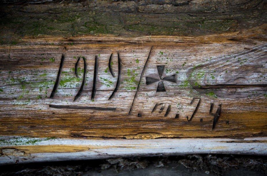 Tvarto sienoje įrėžti simboliai ir skaičiai